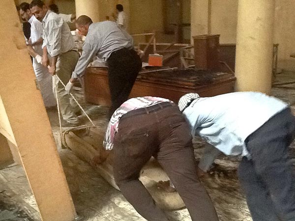 Volunteers and personnel from the Ministry of Antiquities hurry to move heavy objects from the Mallawi Museum before protests begin to roil in the streets once again.